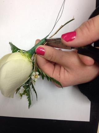 Ajuste solamente los tallos de las hojas verdes y flores de relleno a la misma longitud que el borde de la rosa's stem.
