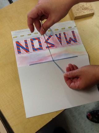 Amarre los dos extremos en un nudo alrededor de las cuerdas corriendo por el pliegue del cuaderno de bocetos. Esto evitará que el nudo de tirar hacia atrás a través del agujero.