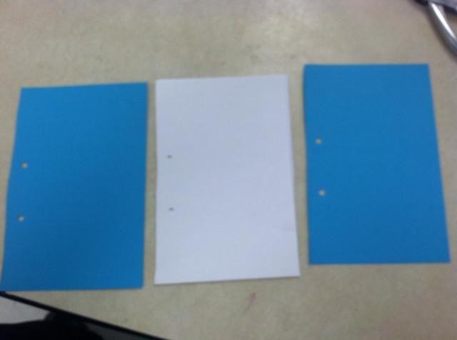 Coloque un papel cartulina delante. Pila de 10 hojas de papel de copia en el centro. Coloque una cartulina en la parte trasera. Asegúrese de que los agujeros están en el mismo lado.