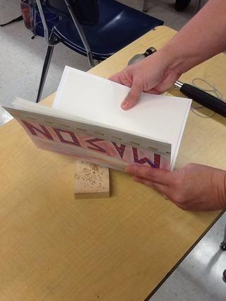 Centrar las páginas dobladas dentro de la cubierta de papel de tarjetas. Coloque el bloque de madera bajo el borde exterior plegada del libro.