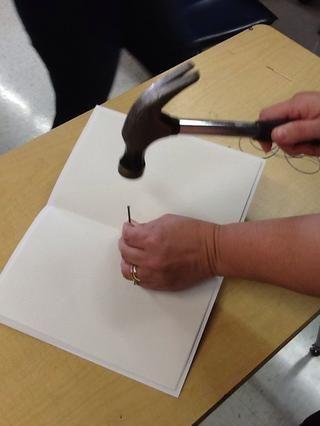 Utilizando un martillo y un clavo, hacer tres agujeros a través de todos los papeles para entrar por el pliegue central. Asegúrese de que el bloque de madera se encuentra en el lugar para proteger la mesa