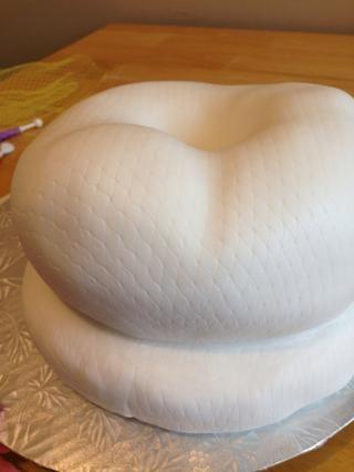 Ligeramente rocía el pastel ganached con una niebla de agua, y poner su pasta de azúcar sobre el pastel, presionando con cuidado en el