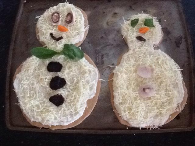 ¡Decorar! Utilizamos champiñones en rodajas, los tomates secados al sol, las zanahorias en rodajas y hojas de espinacas para que las características de nuestros muñecos de nieve.