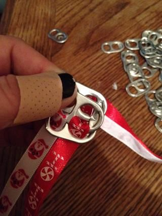 Agarra una tercera pestaña y mantenga por debajo del borde de la segunda pestaña, haciendo agujeros para cintas para enhebrar una copia de seguridad a través.