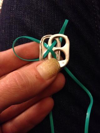 Añadir la siguiente pestaña en la parte superior. Ponga la puntilla final a través del agujero superior. Ponga la tapa del cordón a través del agujero inferior haciendo una X. Usted puede poner la puntilla a través de los mismos orificios si desea.