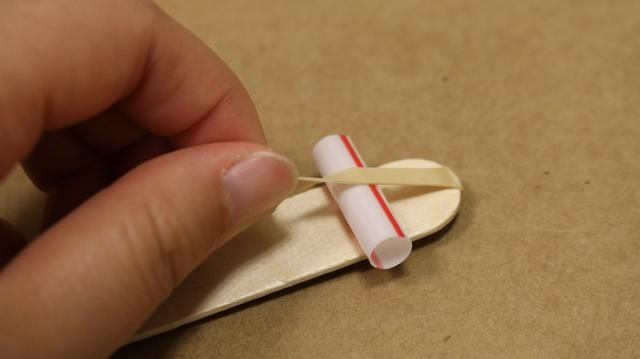 Inserte las dos piezas de la paja bajo su banda de goma