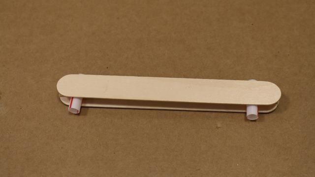 Coloque otro palito de madera en la parte superior, creando en conjunto un sándwich