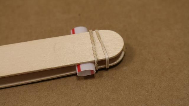 El uso de las bandas de goma de menor tamaño, lo atan alrededor extremos de los palitos de madera. Asegúrese de que está en el exterior de la pajita más cercana al extremo