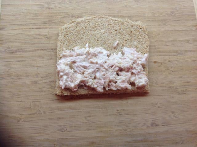 Esparza la mitad del atún y mayonesa combinado en medio del pan aplanado.