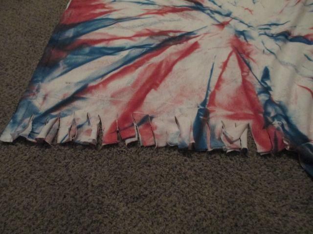 Cortar pequeñas pestañas en la camiseta de 1 pulgada de diferencia. Hacer las pestañas cerca de 1 pulgada de distancia.