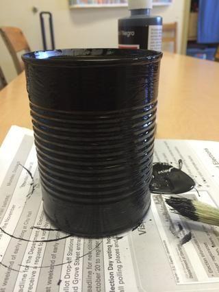 Pintar toda exterior de la lata con pintura negro. Espere a que se seque. Añadir segunda capa de pintura si es necesario.
