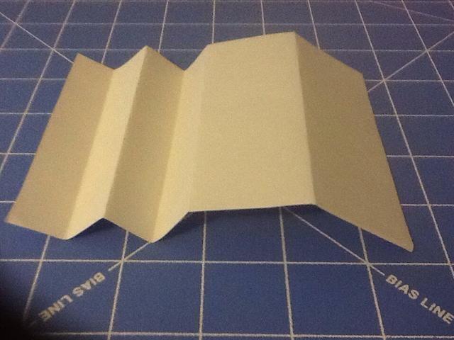 Da la vuelta al papel y traer a los dos pliegues (éstos se llaman montañas) juntos y crear un valle entre el pliegue.