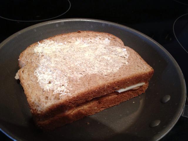 Slap su sándwich abajo (lado de la mantequilla hacia abajo), y luego la mantequilla al otro lado. Usted debe poner el sándwich en principios por lo que el queso tiene tiempo para derretir antes el pan se pone demasiado oscura