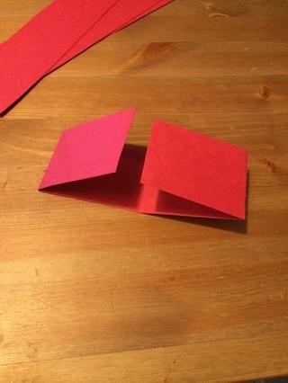 Desdoble el papel y luego doblar cada extremo del centro, alineados en el pliegue.