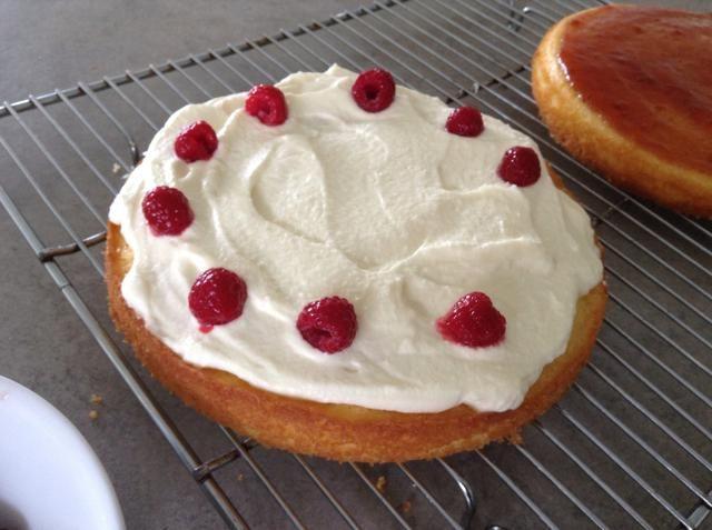 Extender la crema sobre la parte superior de la otra torta y decorar con frambuesas