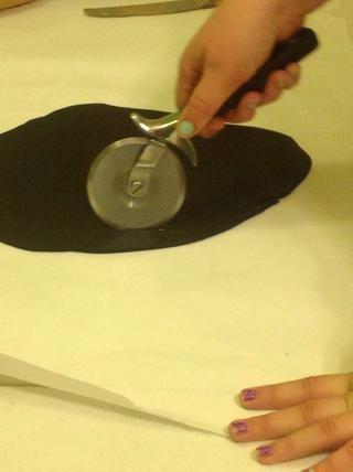 Estirar la pasta de azúcar negro y utilizar un cortador de pizza para crear rayas de la cebra.