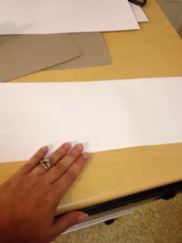 Doble el pedazo largo de papel por la mitad.