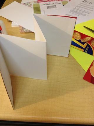 En el frente de la caja de cereal y contraportadas añadir papel decorativo o trabajo de arte a su libreta de acordeón.
