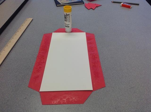 Paso 6: Centrar la cartulina dentro del papel. Pegue sólo las pestañas a la cubierta doblando cuidadosamente alrededor de cada lado. Utilice una barra de pegamento para obtener mejores resultados.