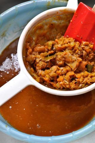 Cuele la mezcla con un colador fino, empujando hacia abajo en las verduras para extraer todo el sabor.
