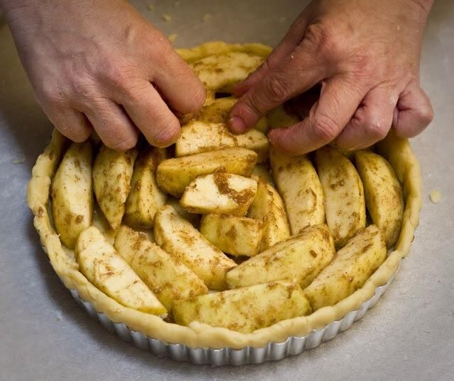 Colocar los trozos de manzana parte cortada hacia abajo en un círculo alrededor del borde exterior de la cacerola. Cortar las rebanadas restantes largo por la mitad y de pie en el centro.