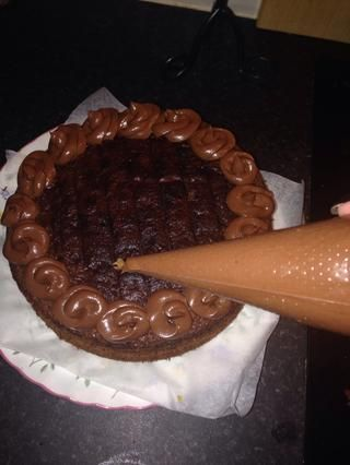 A continuación, utilice una manga pastelera y cuchara el resto del glaseado de chocolate en ella. Crear pequeños remolinos ontop de la torta :)