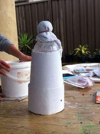 Para hacer que la forma de la bola en la parte superior de la corona que necesita para poner un trapo viejo o una toalla en la parte superior de la botella para formar una bola y poner elástica alrededor.