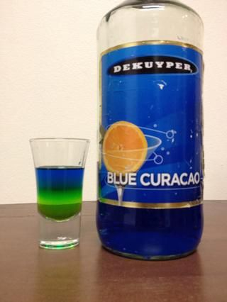 Vierta lentamente en una media onza de Blue Curaçao. Use la parte de atrás de una cuchara para ayudar a la lenta fluidez. Ponte en contacto conmigo para otra forma de verter lentamente. :)