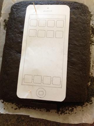 Hornee el pastel. Se trata de un pastel de terciopelo negro en una cacerola 9x13 pulgadas. Receta de Amanda de iambaker.net. yo've used cocktail sticks to hold the template in place and then cut out the shape of the phone.