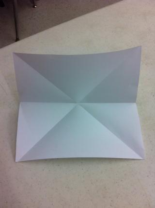 Dobla el papel por la mitad.