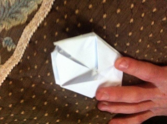 Gire el papel para que pueda ver el final que no tiene aletas. Localice el agujero en la parte superior de este lado.