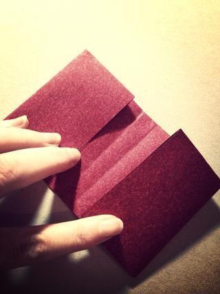 Hoja abierta a continuación, doblar por la mitad horizontalmente. El plegar todos los pliegues para que el libro forma de presentación con solapas