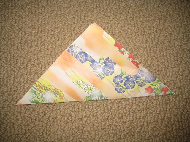 Dobla el papel por la mitad, en diagonal.
