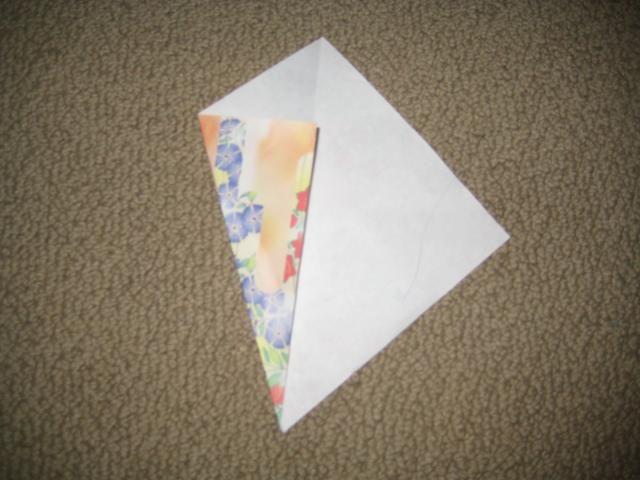 Dale la vuelta para que la línea es recta por el centro. Luego, doblar un lado, en lo que es la mitad de un triángulo en la parte superior.