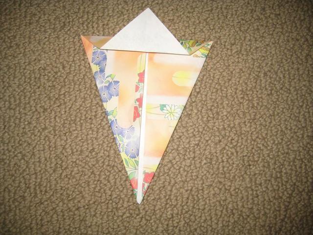 Doble la punta de la parte que acabamos de plegado, habrá un triángulo.