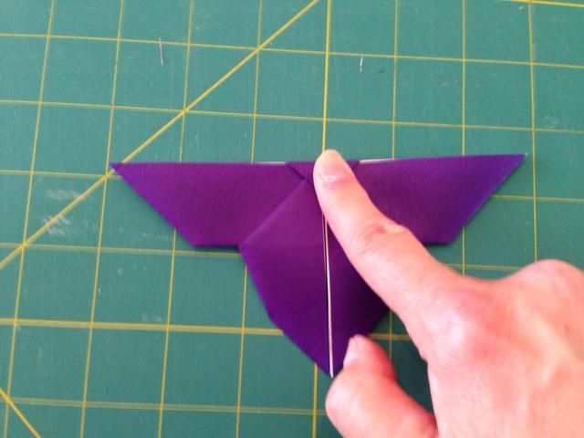Doble la punta hacia abajo, luego doblar el modelo en el medio por la mitad. Vea el siguiente paso para los resultados.