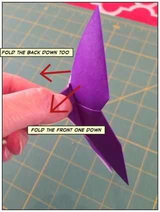 Coge el cuerpo de la mariposa y doblar las alas hacia abajo en un ángulo.