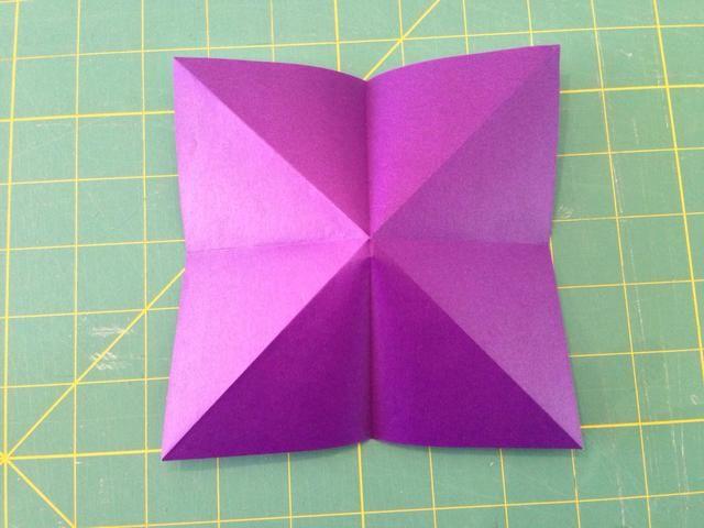 Gire el papel para el lado morado es visible. Sólo aplanar el papel a lo largo arrugas existentes. Vea el siguiente paso para el resultado.
