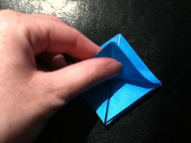 Llevar la punta inferior hasta la parte superior y pliegue, pero llevar la parte inferior hacia abajo.