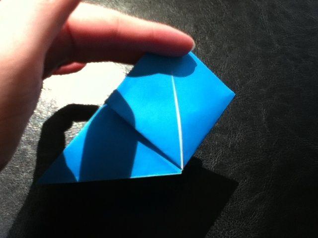 Llevar la punta inferior hasta la parte superior y aplanar.