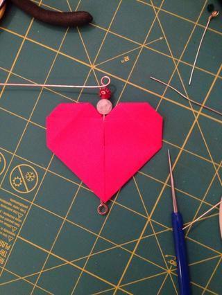 Añadir perlas para el cable y el uso de las pinzas (nariz redonda y nariz de la cadena) para hacer un lazo envuelto en la parte superior.