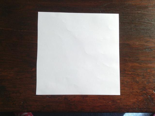 Lleve a su cuadrado de papel y colocarlo sobre una superficie plana. Por ejemplo. Una mesa.