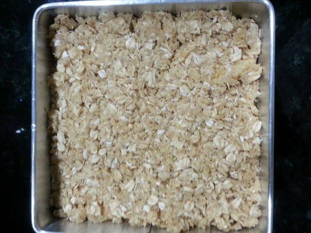 Extienda la mezcla de avena sobre las manzanas y acaricie suavemente.