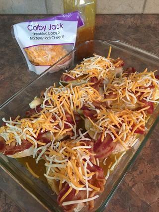 Cubrir con el queso Co-Jack rallado como se muestra. Hornee a 350 ° durante 20 minutos hasta que los jugos salgan claros.