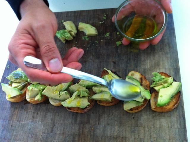 Ahora rociar aceite de oliva sobre el aguacate. Se añade un poco de sabor y sirven para mantener los ingredientes vamos a añadir a continuación. ¡Casi hecho!