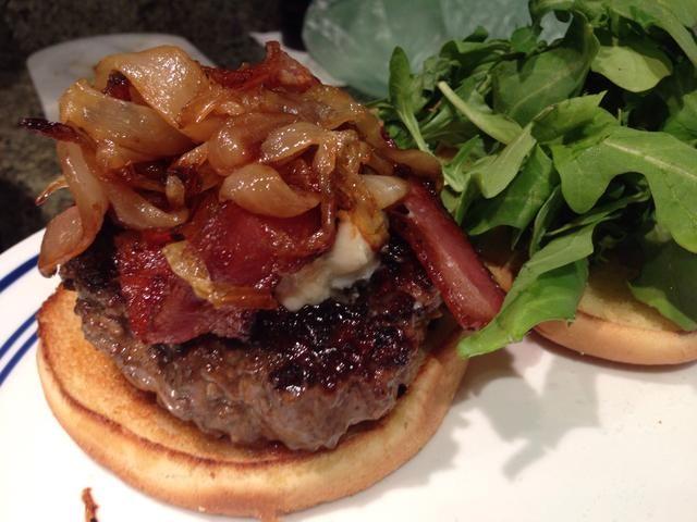 Placa, top hamburguesa con cebolla, coloque una porción de rúcula en la parte superior del bollo.
