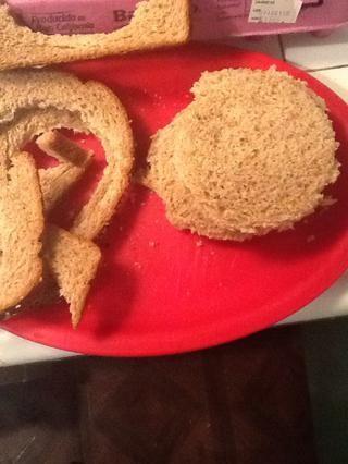 Aplanar las rebanadas de pan con las manos y cortar 8 rondas de 4 pulgadas. A continuación, corte cada ronda por la mitad.
