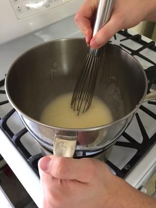 Ajuste el recipiente sobre una olla con agua hirviendo y cocine, revolviendo constantemente, hasta que el azúcar se disuelva completamente y la mezcla registra 140 grados F (unos 6-8 minutos)
