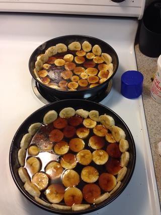 Vierta la mitad de la mezcla de azúcar morena en cada uno de los 2 moldes para pasteles redondos sobre los plátanos.