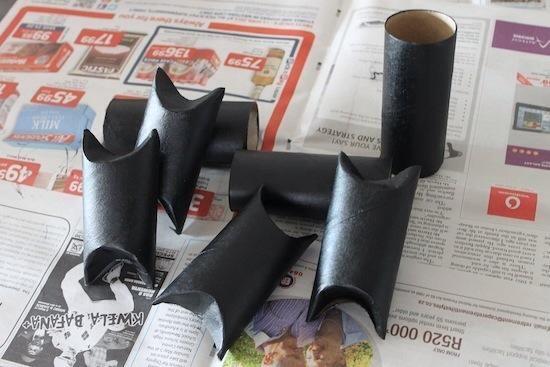 Pinta tu rollos de papel higiénico negro. Deje que se seque. Una vez seco, simplemente doblar en las partes superiores e inferiores de los rollos de papel. Esto formará las cimas puntiagudas y plantas de los titulares de tratar de murciélago.